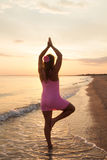 Young girl the beach at sunrise doing yoga Stock Image