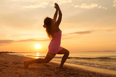 Young girl the beach at sunrise doing yoga exercise Royalty Free Stock Image