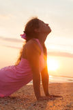 Young girl on beach at sunrise doing yoga exercise Royalty Free Stock Image