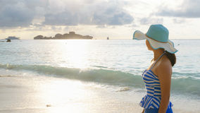 Young girl on the beach at sunrise. Young girl wearing a hat and swimsuit standing watch nature sky and sea during the sunrise on beach of Honeymoon Bay at Koh Stock Images