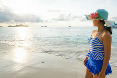 Young girl on the beach at sunrise. Young girl wearing a hat and swimsuit standing watch nature sky and sea during the sunrise on beach of Honeymoon Bay at Koh Royalty Free Stock Image
