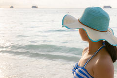 Young girl on the beach at sunrise. Young girl wearing a hat and swimsuit standing watch nature sky and sea during the sunrise on beach of Honeymoon Bay at Koh Stock Photos