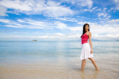 Young girl by the beach turn back look. Young girl with red top standing by the beach turn back and look with blue sky white clouds background Royalty Free Stock Image