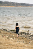 Young girl at the beach walking by the water Royalty Free Stock Image