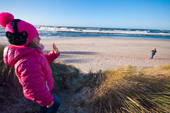 Young girl on beach waving to her mother stock image