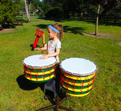 A young girl beating on drums at a park in ontario Royalty Free Stock Photos