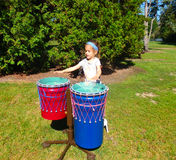 A young girl beating on drums at a park in ontario Stock Photos