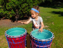 A young girl beating on drums at a park in ontario Royalty Free Stock Photo
