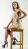 Young girl with a beautiful figure in  trendy golden dress in skin-tight miniskirt and  high heels and platform Royalty Free Stock Image