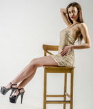 Young girl with a beautiful figure in  trendy golden dress in skin-tight miniskirt and  high heels and platform Stock Photos