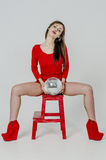 Young girl with a beautiful figure in a trendy red dress in skin-tight miniskirt and red high heels and platform dressed for a pa Royalty Free Stock Photos