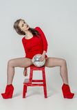 Young girl with a beautiful figure in a trendy red dress in skin-tight miniskirt and red high heels and platform dressed for a pa Royalty Free Stock Images