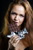Young girl with beautiful make eating chocolate Stock Image