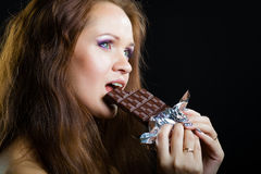 Young girl with beautiful make eating chocolate Stock Images