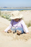 Young girl. A beautiful young girl sitting on the beach Royalty Free Stock Images