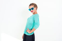 Young girl with a beautiful smile and stylish messy hairstyle wearing blue sunglasses, minty top, posing, standing. Sideways, looking at camera, not isolated Stock Images