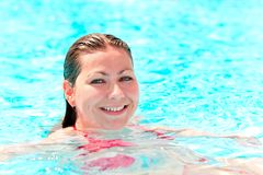 Young  girl with a beautiful smile swim in the pool Royalty Free Stock Images
