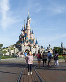 Young girl in beauty sleeping castle in eurodisney. Young girl jumping in front of beauty sleeping castle in disneyland paris Royalty Free Stock Images