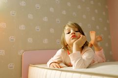 Young girl on bed. Cute young girl lying on mattress in bedroom Stock Images