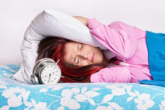 Young girl in bed covering her ears with a pillow from the alarm Stock Image