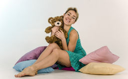 Young girl on a bed with a teddy bear Stock Photos