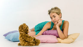 Young girl on a bed with a teddy bear Stock Photography
