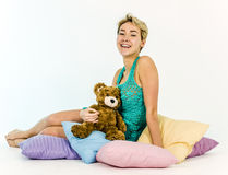 Young girl on a bed with a teddy bear Stock Images