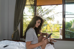 Young Girl On Bed Tropical Hotel Room Interior, Woman Using Cell Smart Phone Tropic Holiday Vacation Stock Photos
