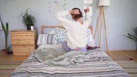 A young girl in bed is tying her hair early in the morning in a cozy and simple Scandinavian interior. 4k stock video footage