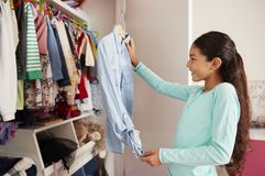 Young Girl In Bedroom Choosing Clothes From Closet royalty free stock photos