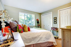 Young girl bedroom with dual closets, and white bedding. Guest bedroom with dual closets, white bedding, and colorful pillows stock images