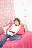Young Girl In Bedroom Playing Handheld Game Stock Image