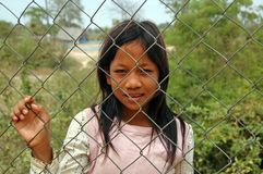 Young Girl Begging for Money at Killing Fields Fence, Cambodia. stock photo
