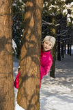 Young girl behind a tree in wood, hiding Royalty Free Stock Photos