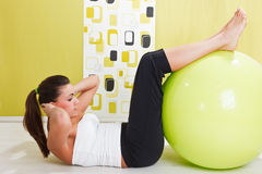 Young Girl Behooves Gym Exercise With Ball Stock Photography
