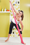 Young Girl Behooves Gym Exercise With Rubb Stock Image