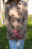Young girl in a beige coat, blue jeans and striped t-shirt. Walks in the park. In her hands a pink purse Stock Images