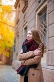 A young girl in a beige coat in the street embraced herself royalty free stock image