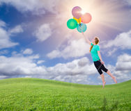Young Girl Being Carried Up and Away By Balloons That She Is Hol Royalty Free Stock Image