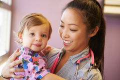 Young Girl Being Held By Female Pediatric Doctor Royalty Free Stock Images
