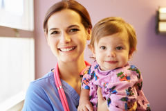 Young Girl Being Held By Female Pediatric Nurse Royalty Free Stock Photography