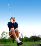 A young girl being pulled on a mono swing. In the playground, showing movement Royalty Free Stock Photo