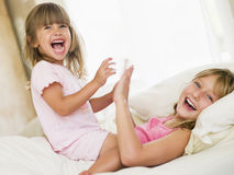 Young Girl Being Woken Up By Her Little Sister Royalty Free Stock Image