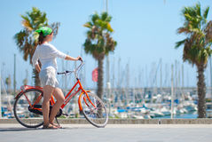 Young girl with a bicycle. On the beach in Barcelona Stock Photography