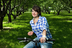 Young girl on a bicycle in the garden Royalty Free Stock Image