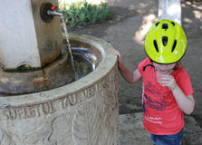 Young girl in a bicycle helmet drinking a glass of water, near a fountain Stock Images