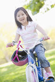 Young girl on bicycle outdoors smiling Stock Images