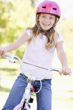 Young girl on bicycle outdoors smiling Royalty Free Stock Images