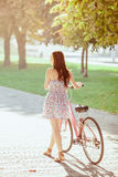 The young girl with bicycle in park Royalty Free Stock Photo