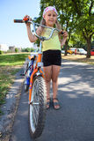 Young girl with a bicycle standing on an asphalt way in park Royalty Free Stock Photography